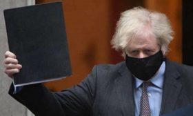 Boris Johnson with roadmap document